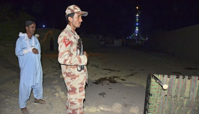 Pakistani security personnel stand guard at the site of a blast in Jhal Magsi, about 400 kilometers (240 miles) east of Quetta, Pakistan, Thursday, Oct. 5, 2017. A suicide bomber struck a Shiite shrine packed with worshippers in a remote village in southwestern Pakistan on Thursday, killing many people and leaving at least 25 wounded, a provincial government spokesman and the police said. (AP Photo/Ayub Khosa)