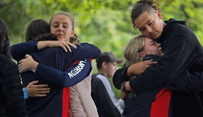 Άνθρωποι αγκαλιάζονται αναστατωμένοι μετά το τραγικό συμβάν στη Νέα Ζηλανδία
