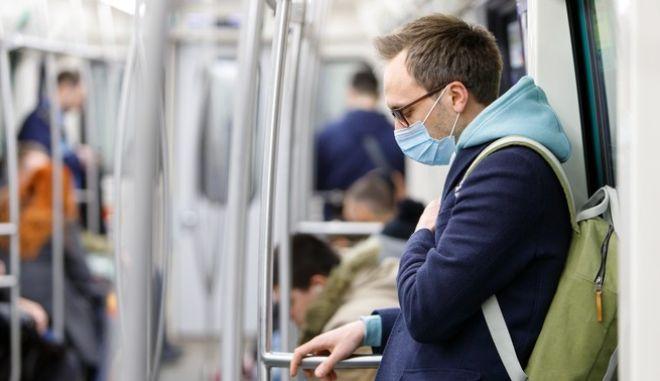 Άνδρας με μάσκα στο μετρό, εν μέσω πανδημίας.