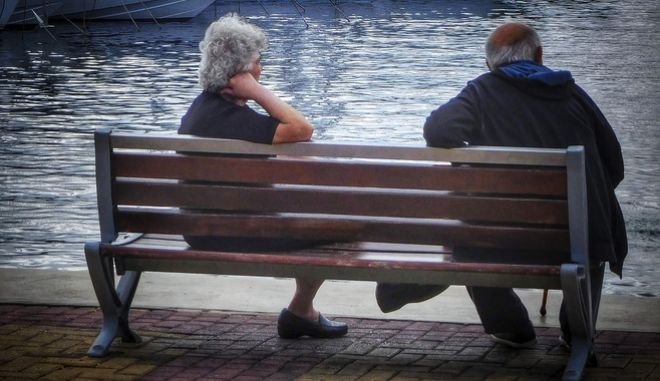 Ηλικιωμένοι κάθονται σε παγκάκι στην Μαρίνα Αλίμου.