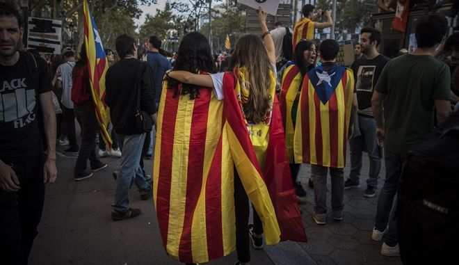 Two girls, one with a Catalan independence flag wrapped on her shoulders walks together with another one with a Spanish flag as demonstrators gather in downtown Barcelona, Spain, Tuesday Oct. 3, 2017. Thousands of people are demonstrated in Barcelona in protest at what they say was police brutality during a referendum on Catalonia's secession from Spain that was previously declared illegal by Spain's Constitutional Court.(AP Photo/Santi Palacios)