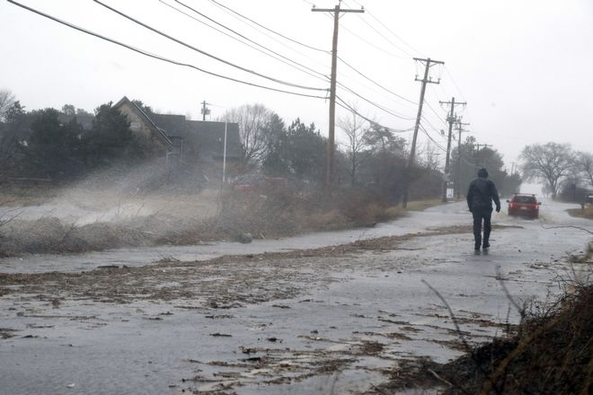 A pedestrian walks down a flooded roadway towards Plum Island Friday, March 2, 2018, in Newburyport, Mass., as a major nor'easter pounds the East Coast, packing heavy rain, intermittent snow and strong winds. The Eastern Seaboard is expected to be buffeted by wind gusts exceeding 50 mph, with possible hurricane-strength winds of 80 to 90 mph on Cape Cod. (AP Photo/Elise Amendola)