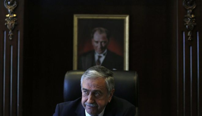 Turkish Cypriot leader Mustafa Akinci is seen at his office in front of the portrait of the Turkish Republic founder Kemal Ataturk, during an interview for the Associated Press in the Turkish breakaway north part of the divided capital Nicosia in this ethnically Mediterranean island of Cyprus, Monday, April 4, 2016. The leader of the breakaway Turkish Cypriots says the ethnically divided islands potential wealth from newly found offshore gas deposits could partly pay for a costly reunification deal. (AP Photo/Petros Karadjias)