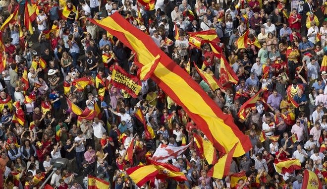 "People wave Spanish national flags as thousands packed the central Cibeles square to in Madrid, Spain, Saturday, Sept. 30, 2017. Thousands of pro-Spanish unity supporters donning Spanish flags have rallied in a central Madrid plaza to protest the Catalan regional government's drive to separate from Spain. Writing on one of the flags reads: ""Long live the Unity of Spain"". (AP Photo/Paul White)"