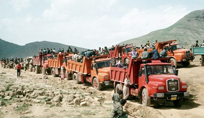 Kurdish refugees travel by truck between their mountain campsites and tent cities established by U.S. military personnel.  Such facilities are being established as part of Operation Provide Comfort, an Allied effort to aid the refugees who fled the forces of Saddam Hussein in northern Iraq.
