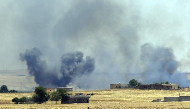 In this photo taken in Akcakale, Sanliurfa province, southeastern Turkey from the Turkish side of the border between Turkey and Syria, smoke from a US-led airstrike rises over the outskirts of Tal Abyad, Syria, Sunday, June 14, 2015. Syrian Kurdish fighters closed in on the outskirts of a strategic Islamic State-held town on the Turkish border Sunday, Kurdish officials and an activist group said, potentially cutting off a key supply line for the extremists' nearby de facto capital. Taking Tal Abyad, some 80 kilometers (50 miles) from the Islamic State stronghold of Raqqa, would mean the group wouldn't have a direct route to bring in new foreign militants or supplies.(AP Photo/Lefteris Pitarakis)