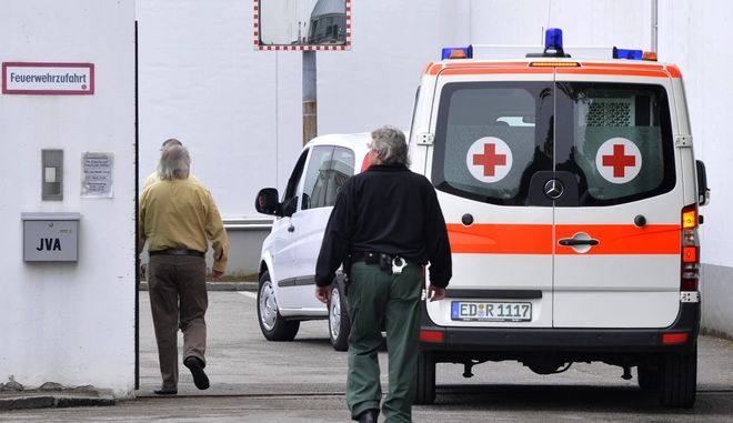 FILE - Judicial officers escort an ambulance car believed to carry suspected Nazi death camp guard John Demjanjuk as drives through the gate of the Stadelheim prison in Munich, southern Germany, on May 12, 2009. The trial against Demjanjuk will start Monday Nov. 30, 2009, in Munich, southern Germany. Demjanjuk is charged with being an accessory to the murder of 27,900 people at the Sobibor death camp in Nazi-occupied Poland, where prosecutors allege he served as a guard. (AP Photo/Uwe Lein)