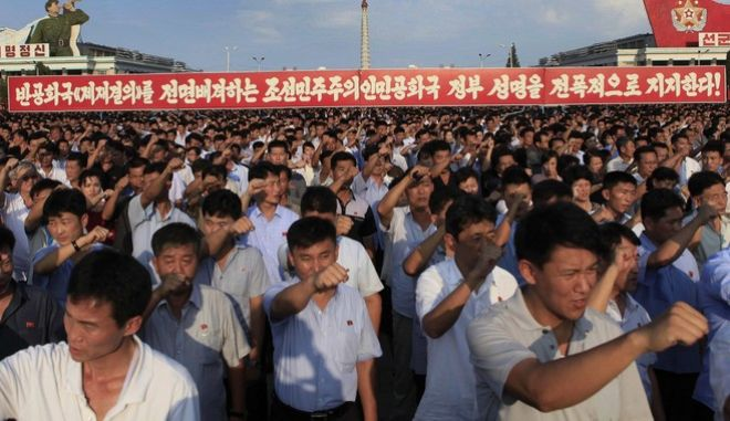 """ADDS TRANSLATION OF SIGN - Tens of thousands of North Koreans gathered for a rally at Kim Il Sung Square carrying placards and propaganda slogans as a show of support for their rejection of the United Nations' latest round of sanctions on Wednesday Aug. 9, 2017, in Pyongyang, North Korea. Propaganda sign at rear says, """"We fully support the government of the Democratic Peoples Republic of Korea that totally rejects the anti-republic sanctions resolution!"""" (AP Photo/Jon Chol Jin)"""