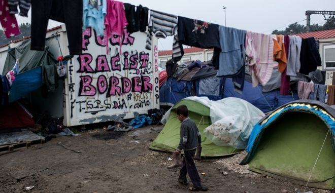 A refugee boy walks among the tents in a refugee camp near the village of Idomeni at the Greek - FYROM border on March 18, 2016.