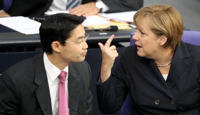 Bundeskanzlerin Angela Merkel (CDU) unterhält sich am Donnerstag (08.09.2011) im Deutschen Bundestag in Berlin mit Bundeswirtschaftsminister Philipp Rösler (FDP). Das Parlament berät über den erweiterten Euro-Rettungsschirm EFSF. In erster Lesung diskutieren die Abgeordneten über den Gesetzentwurf der Koalition, der Ende September endgültig verabschiedet werden soll. Umstritten ist vor allem die Beteiligung des Parlaments bei künftigen Milliardenhilfen für marode Euro-Staaten. Foto: Wolfgang Kumm dpa +++(c) dpa - Bildfunk+++