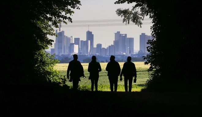 Four young people walk through a forest in Wachenbuchen near Frankfurt, Germany, with the skyline of the Frankfurt banking district in the background, Wednesday, June 7, 2017. (AP Photo/Michael Probst)