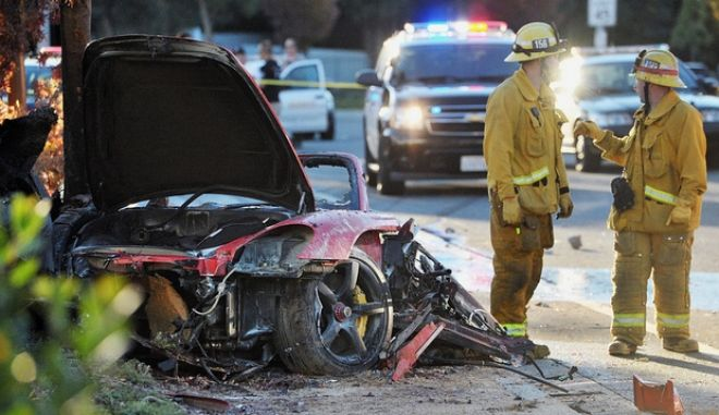 """First responders gather evidence near the wreckage of a Porsche sports car that crashed into a light pole on Hercules Street near Kelly Johnson Parkway in Valencia on Saturday, Nov. 30, 2013. A publicist for actor Paul Walker says the star of the """"Fast & Furious"""" movie series has died in a car crash north of Los Angeles. He was 40. Ame Van Iden says Walker died Saturday afternoon. No further details were released. (AP Photo/The Santa Clarita Valley Signal, Dan Watson)"""