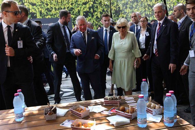 Ο Πρίγκιπας Κάρολος και η σύζυγός του Καμίλα, Δούκισσα της Κορνουάλης, αγοράζουν λουκουμάδες από πλανόδιο πωλητή στην Ερμού