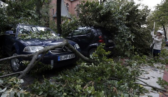 A tree has crashed on cars during a heavy storm in Berlin, Germany, Thursday, Oct. 5, 2017. (AP Photo/Michael Sohn)