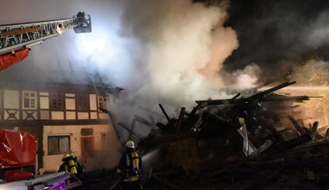 epa04984491 Firefighters try to extinguish a fire mostly inhabited by foreigners in Gudensberg, Germany, 19 October 2015. Some 40 people were inured in the house mostly inhabited by Bulgarian and Polish workers.  EPA/UWE ZUCCHI