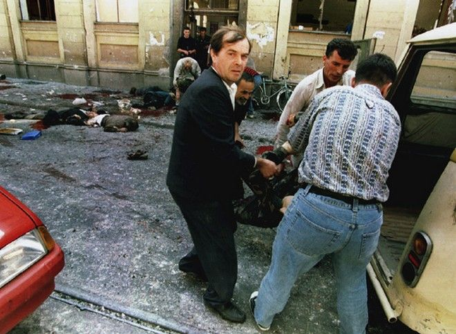 Dead and wounded are loaded into cars outside of the city indoor market after a mortar shell exploded at the entr anceto the building August 28. An artillery shell hit Sarajevo's crowded main street street on Monday, killing at least 32 people and wounding another 40 residents