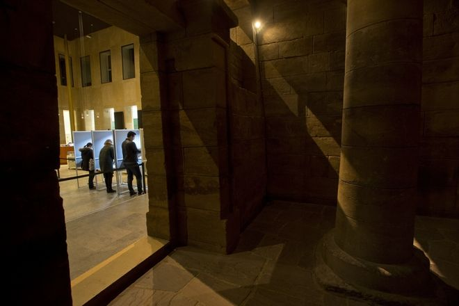 People fill out ballot forms in voting booths, seen from the interior of the ancient Egyptian temple of Taffeh, at the Rijksmuseum van Oudheden or National Museum of Antiquities, in Leiden, Netherlands, Wednesday, March 15, 2017. Amid unprecedented international attention, the Dutch go to the polls Wednesday in a parliamentary election that is seen as a bellwether for the future of populism in a year of crucial votes in Europe. (AP Photo/Peter Dejong)