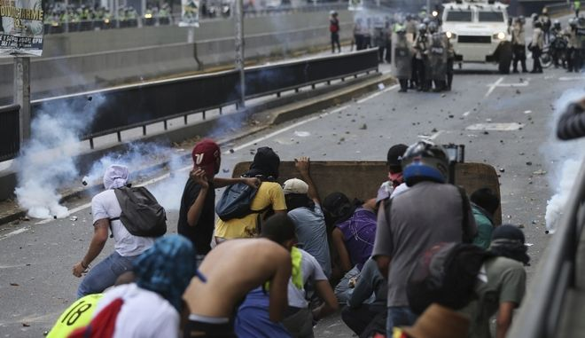 Demonstrators throw stones towards Venezuelan Bolivarian National Police officers during a protest in Caracas, Venezuela, Saturday, April 8, 2017. Opponents of President Nicolas Maduro protested on the streets of the capital as part of an ongoing protest movement that shows little sign of losing steam. (AP Photo/Fernando Llano)