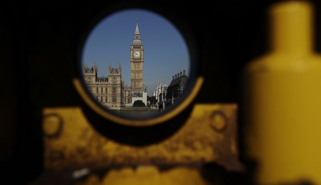 The Houses of Parliament are photographed through a metal stand that used to house a telescope for tourists to use, in London, Monday, June 19, 2017. After almost a year of waffling, Britain finally opens negotiations with its European Union counterparts on Monday about leaving the bloc. (AP Photo/Matt Dunham)