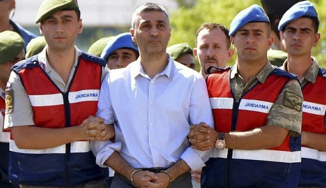 Turkish Army officers escort a man accused of attempting to kill Turkey's President Recep Tayyip Erdogan on the night of the July 15, 2016 failed coup attempt, to a court in Mugla, southwesternTurkey, Wednesday, Oct. 4, 2017. The court sentenced 40 suspects, most of them former military personnel, to life in prison Wednesday, convicting them of charges that include attempting to kill Erdogan during last year's failed coup. (Cavit Akgun/DHA-Depo Photos via AP)
