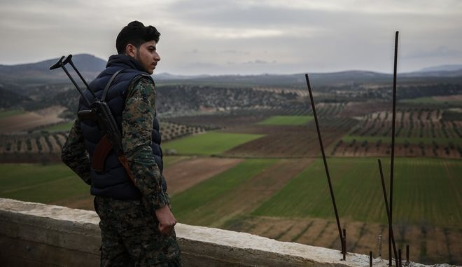 A Turkey-backed opposition fighters of the Free Syrian Army looks on from Mersewa village, in the greater Afrin district, Syria, during a Turkish government-organised media tour into northern Syria, Saturday, March 3, 2018. Already in the sixth week of its offensive on the Kurdish-held enclave of Afrin in northwestern Syria, Turkey wants to oust the Syrian Kurdish People's Protection Units, or YPG, from Afrin. It considers the group an extension of a Kurdish insurgency within its own borders. (AP Photo/Emrah Gurel)