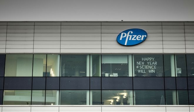 A sign in the window of an office at Pfizer Manufacturing in Puurs, Belgium on Monday, Dec. 21, 2020. The European Medicines Agency is meeting Monday to consider approving a coronavirus vaccine developed by BioNTech and Pfizer that would be the first to be authorized for use in the European Union. The closed-doors meeting comes weeks after the shot was granted permission under emergency provisions by regulators in Britain and the United States. (AP Photo/Valentin Bianchi)