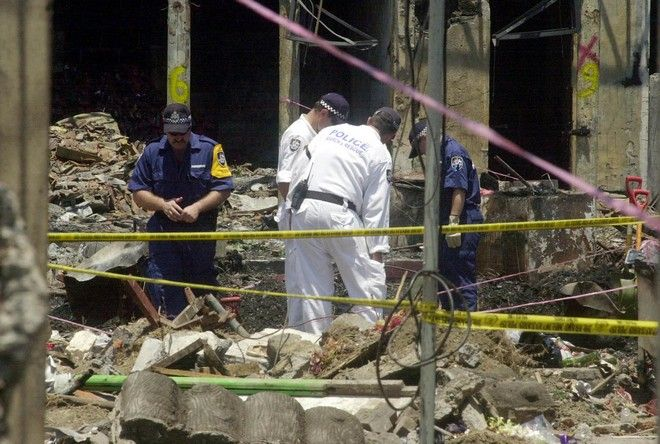 Australian police officers continue to investigate at the ruins of the Sari Club, which was flattened by a bomb attack on Oct. 12, in Kuta, Bali, Monday, Oct. 21, 2002. The nightclub bombing killed more than 180 people and injured 300. (AP Photo/Achmad Ibrahim)
