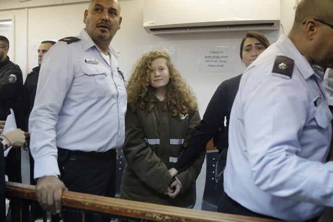 CORRECTS NAME OF PHOTOGRAPHER TO MAHMOUD ILLEAN -- Ahed Tamimi is brought to a courtroom inside the Ofer military prison near Jerusalem, Monday, Jan. 15, 2018. Tamimi, 16, was filmed in December pushing, kicking and slapping Israeli soldiers, who stood by silently. Her father said the girl was upset after her 15-year-old cousin was shot in the head with a rubber bullet. (AP Photo/Mahmoud Illean)