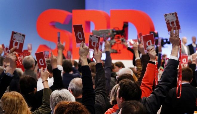 Delegates vote for coalition talks with Chancellor Angela Merkel's conservatives during a party meeting of the Social Democrats, SPD, in Bonn, Germany, Sunday, Jan. 21, 2018. (AP Photo/Michael Probst)