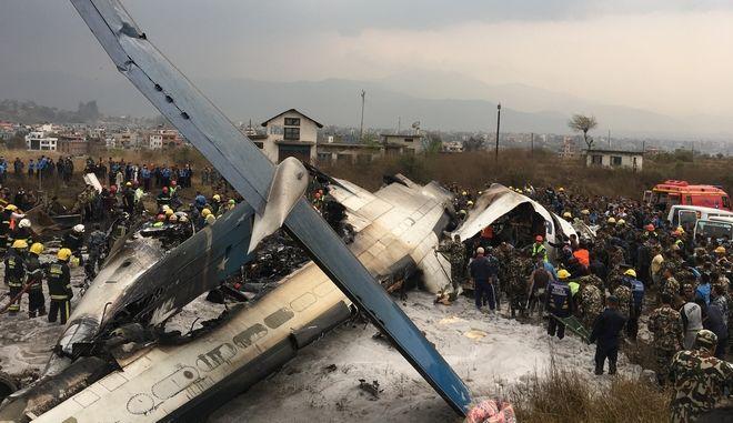 Nepalese rescuers stand near a passenger plane from Bangladesh that crashed at the airport in Kathmandu, Nepal, Monday, March 12, 2018. (AP Photo/Niranjan Shreshta)