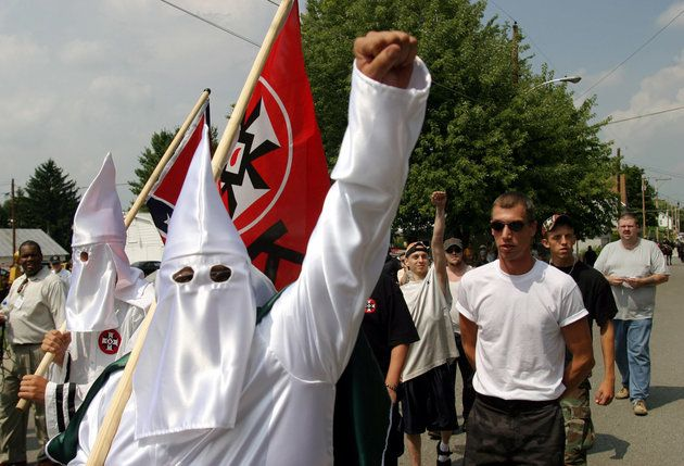Members of the World Knights of the Ku Klux Klan as they march along a street, Saturday, Aug. 28, 2004, in Sharpsburg, Md. The participants in the march were outnumbered by more than two dozen police in riot gear who kept the Klansmen away from scores of people gathered in a downtown intersection. The police escorted the marchers to a city park, but kept the public away. (AP Photo/Timothy Jacobsen)