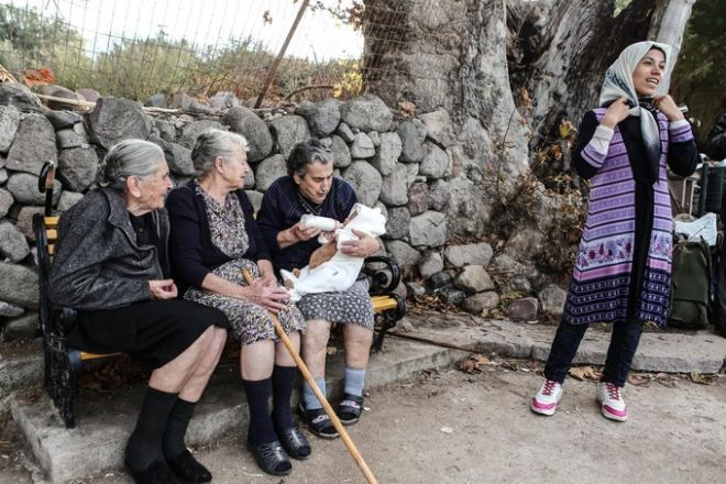 Three elderly women feed a migrant child at the island of Lesbos, Greece on October 17, 2015. /          ,  17  2015.
