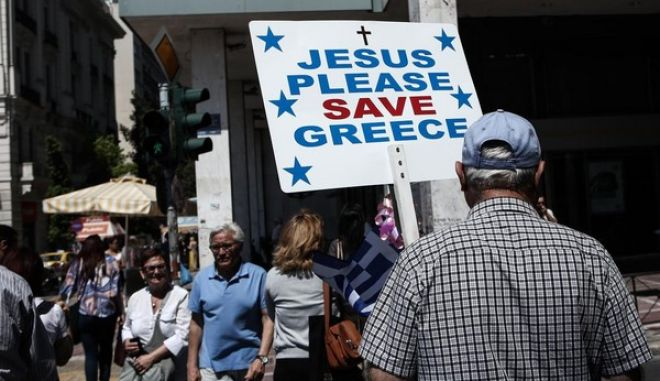 A man holding a sign that reads Jesus Please Save Greece, strolls around downtown Athens, on June 3, 2015 /     ,    ,  3 , 2015