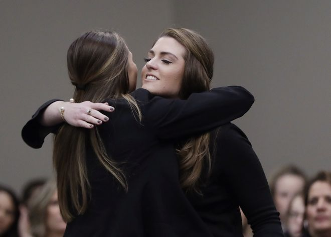 Sterling Riethman, right, is hugged after giving her victim impact statement during the seventh day of Larry Nassar's sentencing hearing Wednesday, Jan. 24, 2018, in Lansing, Mich. Nassar has admitted sexually assaulting athletes when he was employed by Michigan State University and USA Gymnastics, which is the sport's national governing organization and trains Olympians. (AP Photo/Carlos Osorio)