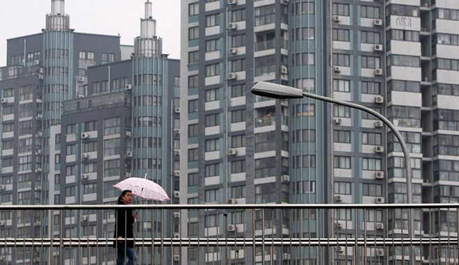 epa03646651 A Chinese woman walks on a pedestrian overpass near an apartment area in Qingdao city, eastern China's Shandong province, 01 April 2013. Many Chinese cities announced their detailed property curbs policy at the end of March in order to further cool the real estate market amid expectations of rising property prices this year.  EPA/WU HONG