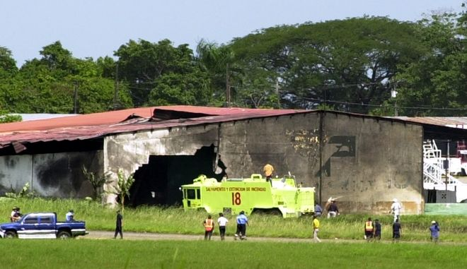 Ambulances and firefighting vehicles are parked outside as workers inspect the hangar where U.S.-registered small jet apparently being used to ferry a patient from Ecuador to Washington, D.C. crashed at a Panama City airport, Friday, July 2, 2004. Four people were killed.( AP Photo/Arnulfo Franco)