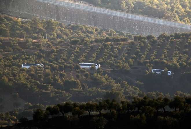 A convoy of buses believed to be carrying Syrian opposition fighters, travels along the border with Syrias as see from the outskirts of the border town of Kilis, Turkey, Saturday, Jan. 20, 2018. Turkish jets have begun an aerial offensive, codenamed operation