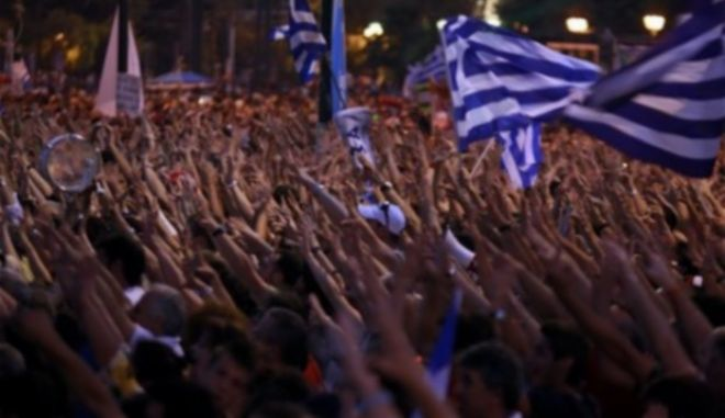 Greek protesters, some waving national flags, gesture at Syntagma square in front of the Greek Parliament in central Athens, during a peaceful ongoing rally against plans for new austerity measures, Tuesday, June 21 , 2011. Demonstrators had camped outside parliament since May 25, 2011.(AP Photo/Lefteris Pitarakis)