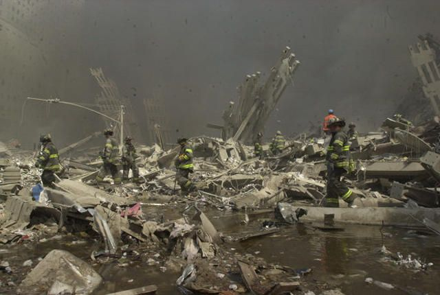 Firefighters and rescue personnel search through rubble of World Trade Center after it was  hit by two hijacked planes in a terrorist attack.  firefighter collapse ground zero