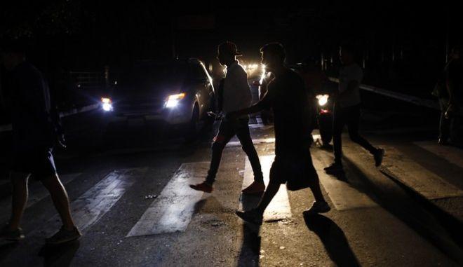 Άνθρωποι στη Βενεζουέλα περνούν τον δρόμο κατά τη διάρκεια ενός black out