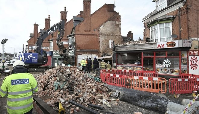 Emergency services at the scene in Leicester, Tuesday Feb. 27, 2018, where emergency services are still searching for victims after an explosion which destroyed a building on Sunday. British police said Wednesday Feb. 28, 2018, they have arrested three men in connection with the explosion that killed five people. (Aaron Chown/PA via AP)