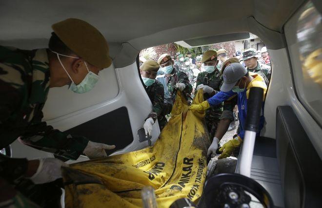 Στρατιώτες μαζεύουν και μεταφέρουν τα πτώματα μετά το φονικό τσουνάμι