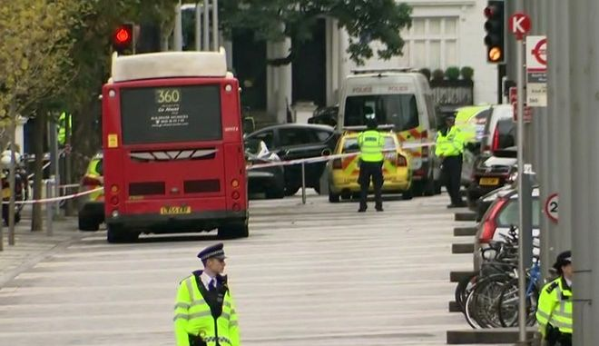 In this image taken from TV, police officers surround the scene of an incident involving a car, at center, in central London, Saturday, Oct. 7, 2017. British emergency services raced to London's Natural History Museum after a car struck pedestrians Saturday outside the building. Police said a number of people were injured and one person was detained at the scene. (AP Photo)