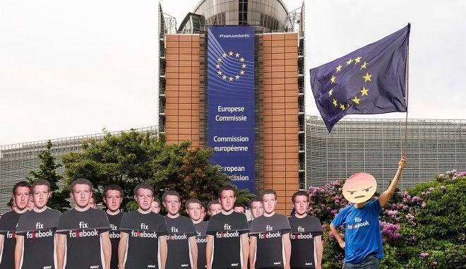 Διαδηλωτής υψώνει τη σημαία της ΕΕ και στέκεται δίπλα σε χάρτινο ομοίωμα του Ζάκερμπεργκ, διαμαρτυρόμενες εναντίον των fake λογαριασμών του Facebook, μπροστά στο κτίριο της Ευρωπαϊκής Επιτροπής στις Βρυξέλλες.