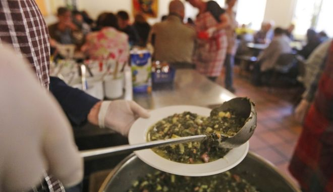 In this picture taken Nov. 3, 2014 a plate is filled up with green cabbage, a traditional meal in Germany, at a soup kitchen for poor people in Dortmund, Germany. Twenty five years after the fall of the Berlin Wall, the disparities that remain between former West and East Germany are a common theme. Unemployment is higher in the east, disposable incomes are lower and the populations are older as the young move west for better opportunities. But the broad-brush look at unified Germany glosses over some major exceptions as Dresden and Dortmund. (AP Photo/Frank Augstein)