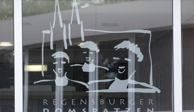 FILE - This Oct. 12, 2016 file photo shows the logo of the Regensburger  Domspatzen choir at a window of the high school in Regensburg.  A report has found that at least 547 members of a prestigious Catholic boys choir in Germany were physically or sexually abused between 1945 and the early 1990s. Allegations involving the Domspatzen choir in Regensburg were among a spate of revelations of abuse by Roman Catholic clergy in Germany that emerged in 2010. News agency dpa reported that Ulrich Weber, a lawyer tasked with investigating the abuse, said Tuesday July 18, 2017  there was violence against children in the choirs pre-school and high school.   (Armin Weigel/dpa via AP,file)
