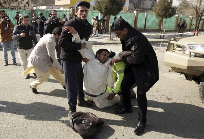 A wounded man is assisted at the site of a deadly suicide attack in the center of Kabul, Afghanistan, Saturday, Jan. 27, 2018. Afghan Public Health Ministry says dozens have been killed and over 100 wounded in suicide car bomb attack in capital Kabul. (AP Photo/Massoud Hossaini)