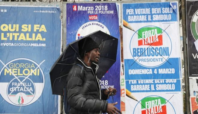 Musab Badur, 23, from Sudan, walks past electoral posters for Italy's general elections, in Milan, Italy, Saturday, March 3, 2018. An election in Italy on Sunday will determine the makeup of the nation's Parliament and its next government. (AP Photo/Antonio Calanni)
