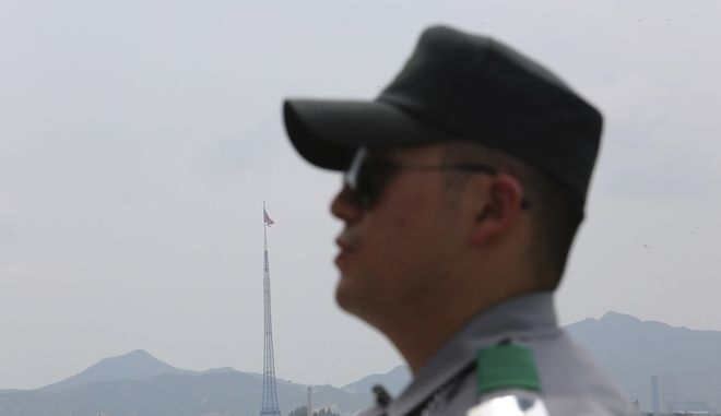 A giant North Korean flag flutters from a 528-foot pole in the propaganda village of Kijong-dong as a South Korean army soldier stands guard at the border villages of Panmunjom in Paju, South Korea, Wednesday, July 19, 2017.  (AP Photo/Ahn Young-joon)