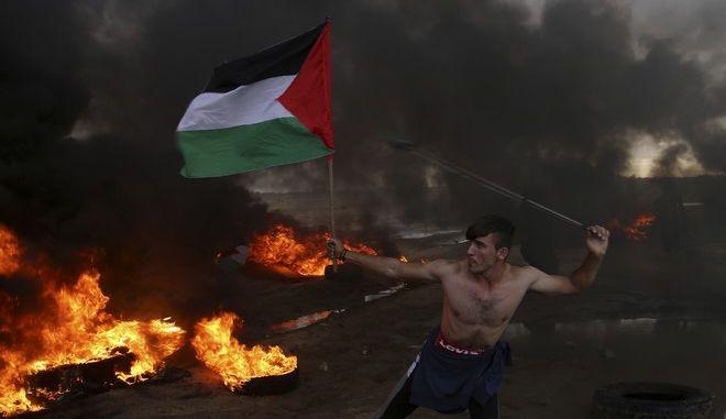 Παλαιστίνιος διαδηλωτής κοντά στον φράκτη που χωρίζει τη Γάζα από το Ισραήλ